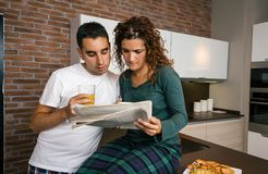 Couple having breakfast and reading newspaper Stock Images