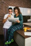 Couple having breakfast and reading newspaper Stock Image