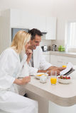 Couple having breakfast while reading newspaper in kitchen Royalty Free Stock Photo
