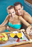 Couple having breakfast in swimming pool Stock Image