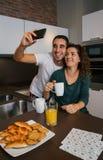 Couple having breakfast and taking selfie Stock Photo