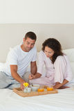 Couple having breakfast in their bed Royalty Free Stock Images