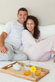 Couple having breakfast in their bed Stock Image