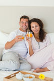 Couple having breakfast in their bed Royalty Free Stock Photo