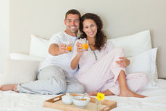 Couple having breakfast in their bed Stock Photography