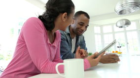 Couple Having Breakfast And Using Digital Tablet In Kitchen stock video footage