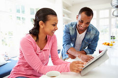 Couple Having Breakfast And Using Digital Tablet In Kitchen Royalty Free Stock Photo