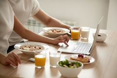 Couple having breakfast using laptop on dining table, close up. Couple having oatmeal and pancakes on breakfast using laptop on dining table, men and women Stock Photo