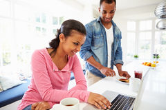 Couple Having Breakfast And Using Laptop In Kitchen Stock Photo