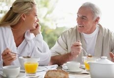 Couple having a chat while at breakfast table Stock Photos