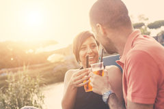 Couple having a cocktail outdoor at sunset. Couple having a cocktail and toasting outdoor on summer. The bar is next to a river, backlight scene at sunset. They royalty free stock photo