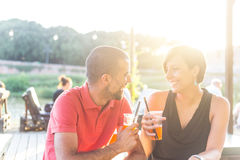 Couple having a cocktail outdoor at sunset. Couple having a cocktail and toasting outdoor on summer. The bar is next to a river, backlight scene at sunset. They royalty free stock images