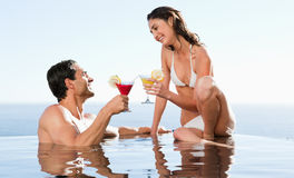 Couple having cocktails in the pool Royalty Free Stock Image