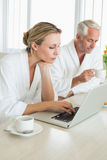 Couple having coffee at breakfast in bathrobes using laptop Royalty Free Stock Photos