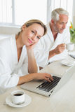 Couple having coffee at breakfast in bathrobes using laptop Stock Images