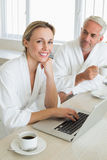 Couple having coffee at breakfast in bathrobes using laptop. At home in the kitchen stock photography