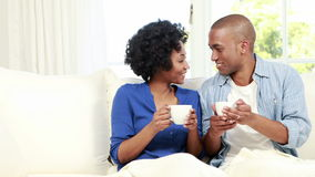 Couple having coffee on the couch. In living room stock footage
