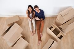 Couple having coffee on floor in new home Stock Photos