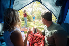 Couple having coffee and looking at kids playing outside the tent Stock Photos