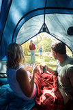 Couple having coffee and looking at kids playing outside the tent Stock Photo
