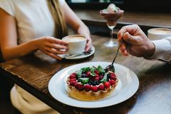 Couple having coffee with nice desserts in a cafe. royalty free stock photo