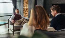 Couple having a counseling session with psychologist. Psychologist listening to couple during therapy session. Psychotherapist understanding the problems of Royalty Free Stock Photography