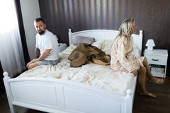 Couple having crisis in bed. Woman sitting on bed`s edge royalty free stock images