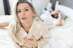 Couple having crisis in bed. Woman sitting on bed`s edge stock photography