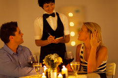 Couple having dinner. Young couple place dinner order to waitress in a restaurant Stock Photo