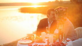 A couple having dinner on the beach at sunset. Honeymoon concept, Man and Woman in love, Couple enjoying glass of champagne on tropical beach at sunset stock video footage