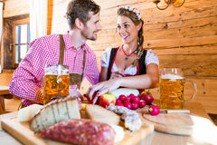 Couple having dinner at mountain hut in alps. Drinking beer and eating cold cuts stock photography