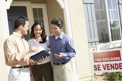 Couple Having Discussion With Agent. Happy couple having discussion with real estate agent in front of their new house Stock Images