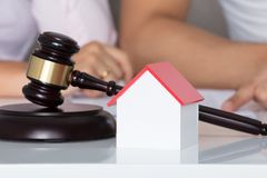 Couple Having Discussion Over Property After Divorce. Behind House Model And Gavel Stock Photo
