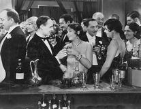 Couple having drink at crowded bar. (All persons depicted are no longer living and no estate exists. Supplier grants that there will be no model release issues Stock Images