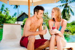 Couple having drinks by the pool Stock Photo