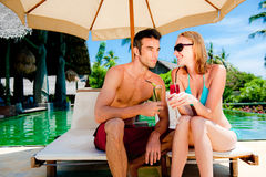 Couple having drinks by the pool Royalty Free Stock Photo