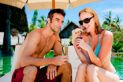 Couple having drinks by the pool Stock Photography