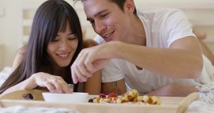 Couple having fruit and waffle breakfast in bed stock footage