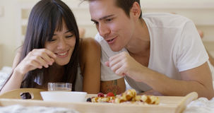 Couple having fruit and waffle breakfast in bed Royalty Free Stock Photos