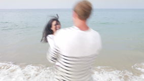 Couple Having Fun On Autumn Beach Together. Couple spinning around together in surf on autumn beach holding hands. Shot on Canon 5d Mk2 with a frame rate of stock video footage