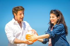 Couple having fun with a beach ball Stock Photos