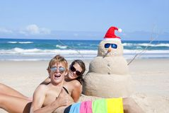Couple having fun at beach with sandman Stock Photo