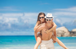 Couple having fun on the beach of a tropical ocean. Happy couple piggybacking cheerful on beach during summer holidays vacation. couple in love having fun on Stock Photography