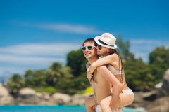 Couple having fun on the beach of a tropical ocean. Royalty Free Stock Image
