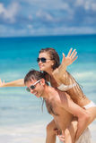 Couple having fun on the beach of a tropical ocean. Stock Image