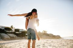 Couple having fun on the beach. Young men carrying attractive women on shoulders while spending carefree time on the beach outdoors. Couple having fun on the Royalty Free Stock Image
