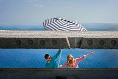Couple having fun with big umbrella on the blue water background Royalty Free Stock Images