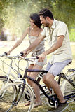 Couple having fun by bike on holiday to the lake Royalty Free Stock Photography