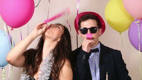 Couple having fun blowing party horn in photo booth. Cute couple having fun blowing party horn in photo booth stock footage