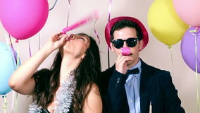 Couple having fun blowing party horn in photo booth. Cute couple having fun blowing party horn in photo booth, graded stock footage